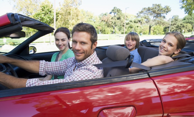 family of four in red convertible